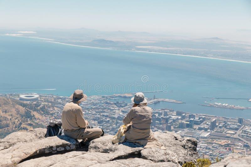 Pares europeus adultos nos chapéus que admiram a vista de Cape Town e do oceano da parte superior da montanha da tabela em Cape T fotos de stock royalty free