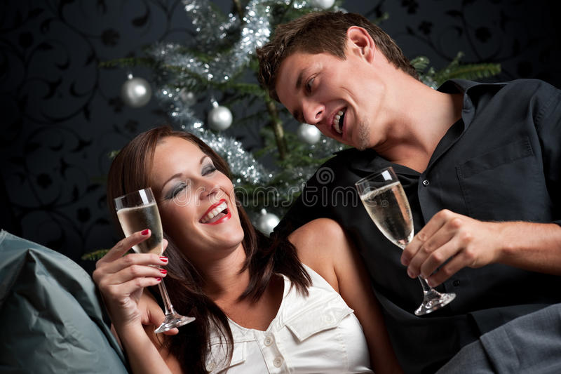 Pares extravagantes con champán en la Navidad foto de archivo