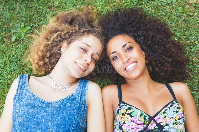 Pares fêmeas multirraciais de amigos que encontram-se na grama fotografia de stock