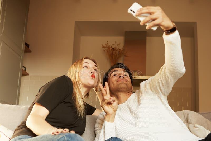 Pares felices alegres de amor que toman el selfie en el sofá en casa fotos de archivo