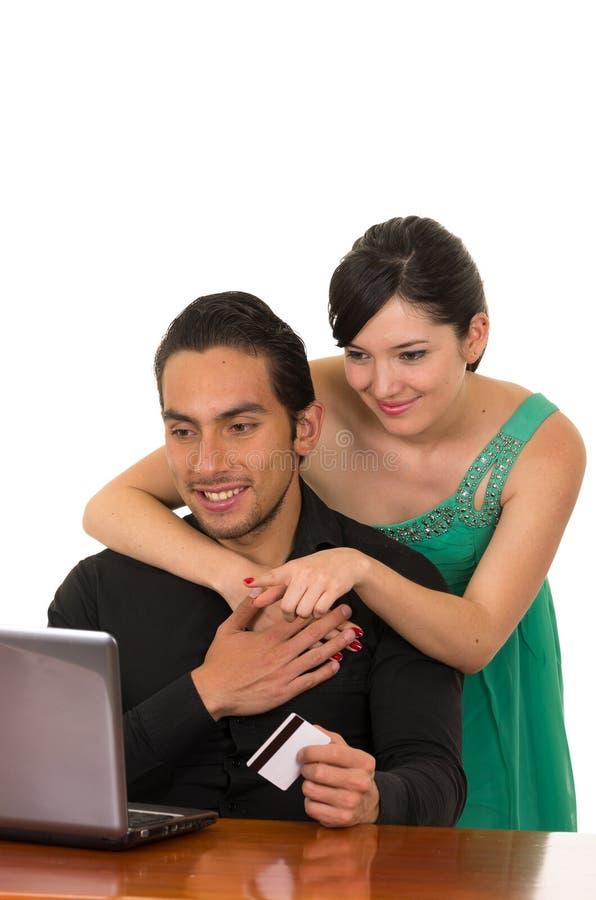 Pares felices atractivos jovenes delante del ordenador fotos de archivo libres de regalías