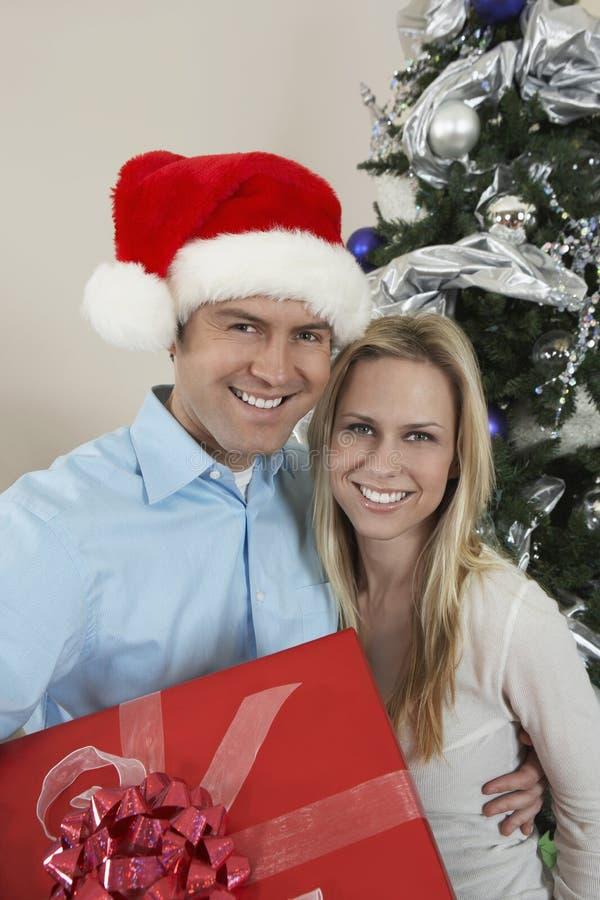 Pares felices con el árbol de navidad que hace una pausa de la caja de regalo imagen de archivo libre de regalías