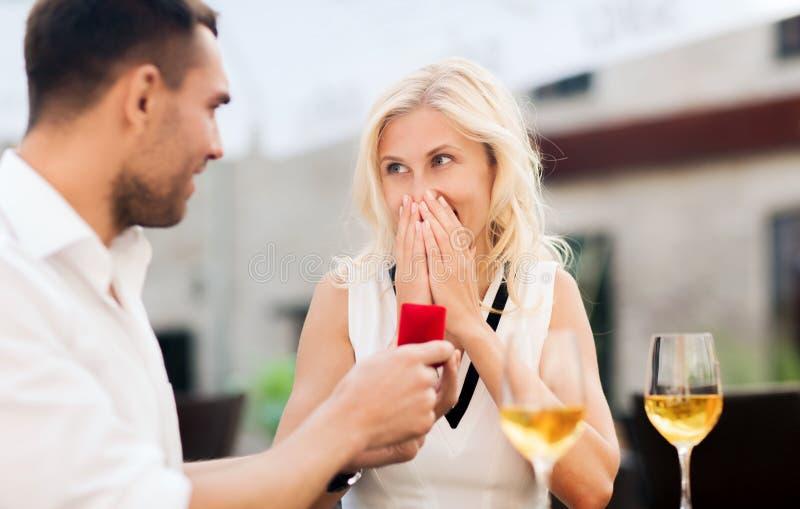 Pares felices con el anillo de compromiso y el vino en el café imagenes de archivo