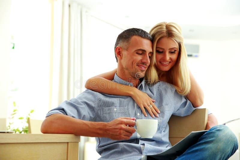 Pares felices con el café, leyendo las noticias foto de archivo libre de regalías