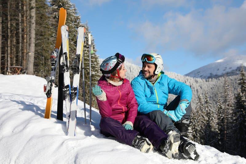 Pares felices con el equipo del esquí que se sienta en nieve Vacaciones del invierno fotos de archivo libres de regalías