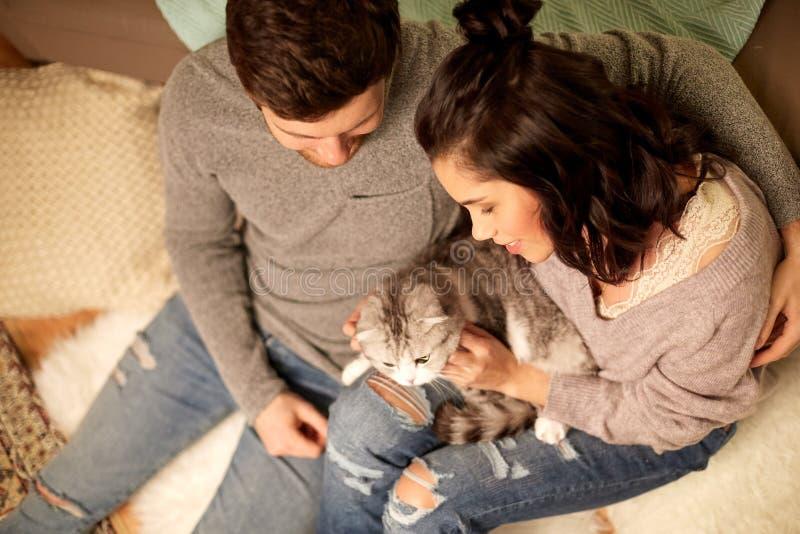 Pares felices con el gato en casa imágenes de archivo libres de regalías