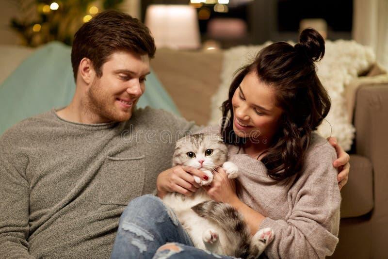 Pares felices con el gato en casa imagen de archivo
