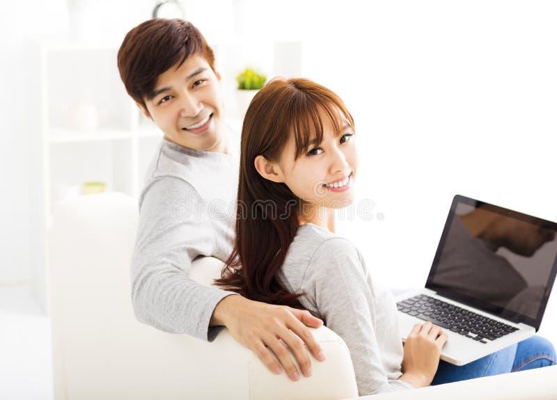 Pares felices con el ordenador portátil en sala de estar imagenes de archivo