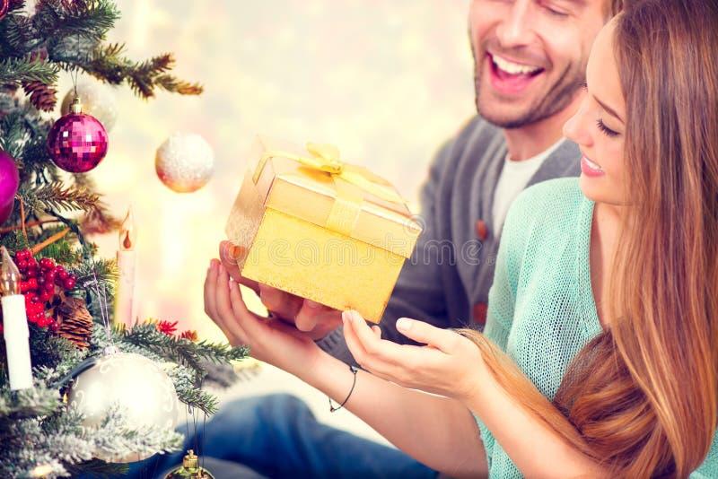 Pares felices con el regalo de la Navidad fotografía de archivo