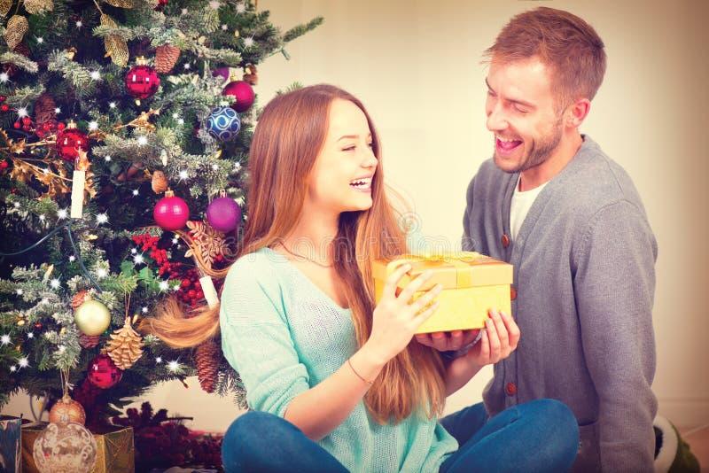 Pares felices con el regalo de la Navidad en casa imagen de archivo