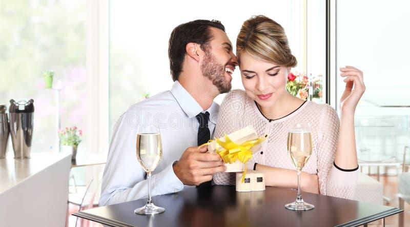 Pares felices con el regalo que se sienta en una tabla con el vino fotografía de archivo libre de regalías