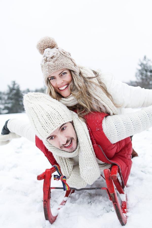 Pares felices con el trineo en invierno imagen de archivo libre de regalías