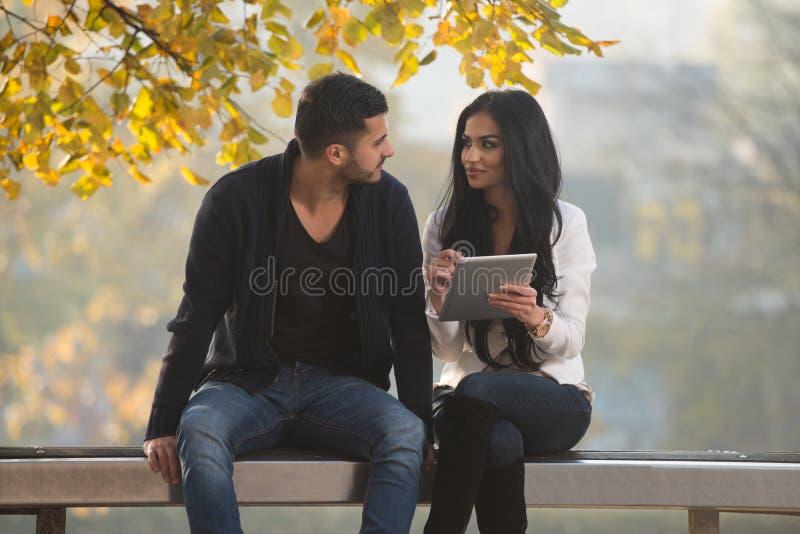 Pares felices con la tableta en el parque imagen de archivo libre de regalías