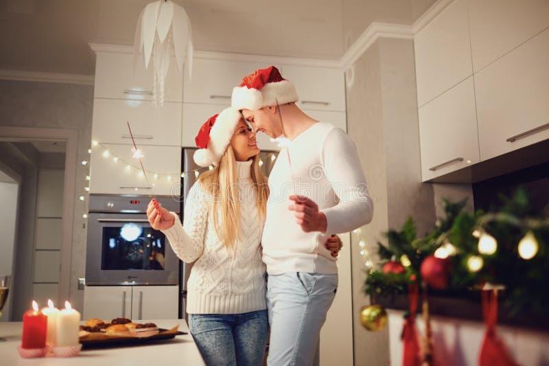 Pares felices con las bengalas en casa para la Navidad fotos de archivo