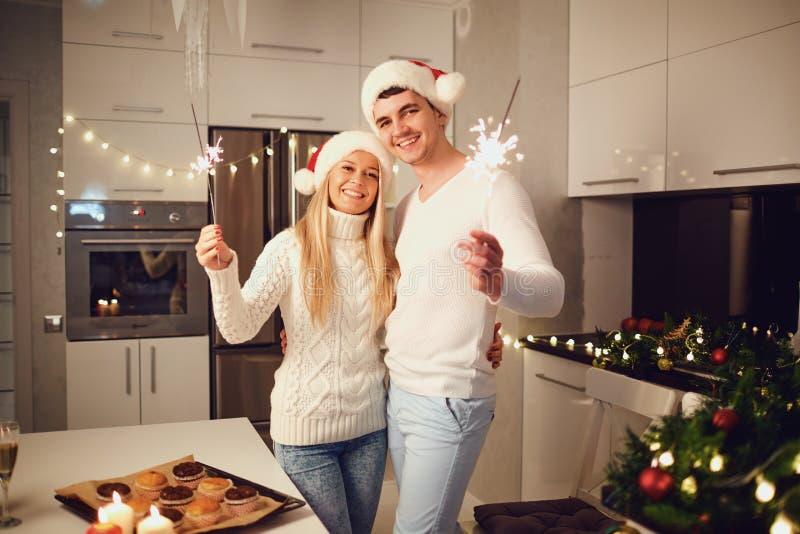 Pares felices con las bengalas en casa para la Navidad imagen de archivo