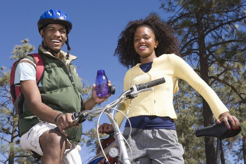 Pares felices con las bicis de montaña foto de archivo libre de regalías
