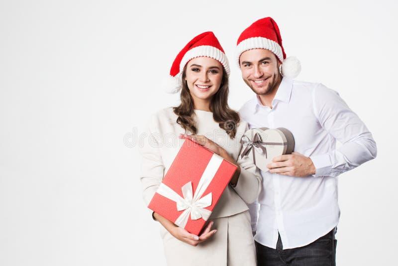 Pares felices con las cajas de regalo sobre el fondo blanco imagen de archivo libre de regalías