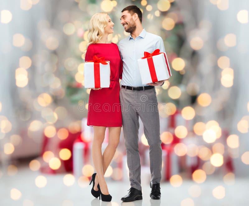 Pares felices con las cajas de regalo sobre luces de la Navidad imagen de archivo libre de regalías