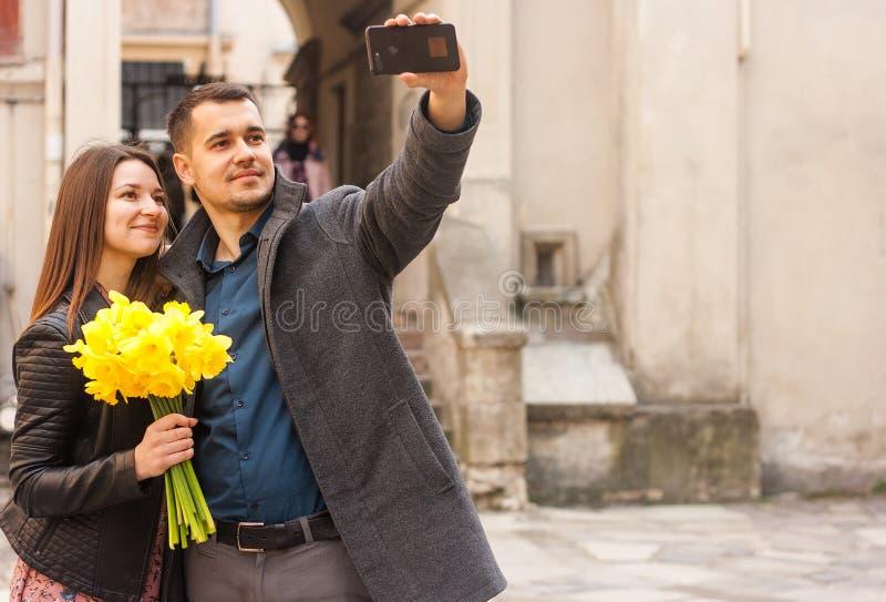 Pares felices con las flores que hacen el selfie en la calle Copie el espacio imagenes de archivo