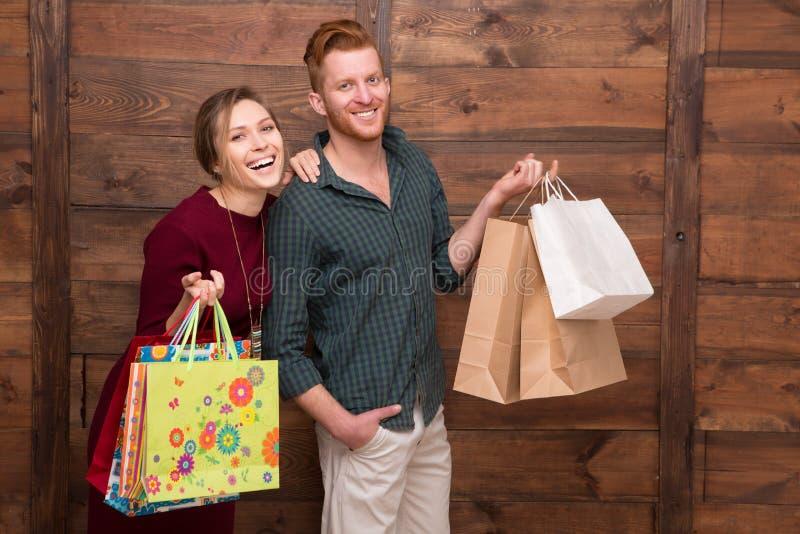 Pares felices con los bolsos de compras fotos de archivo