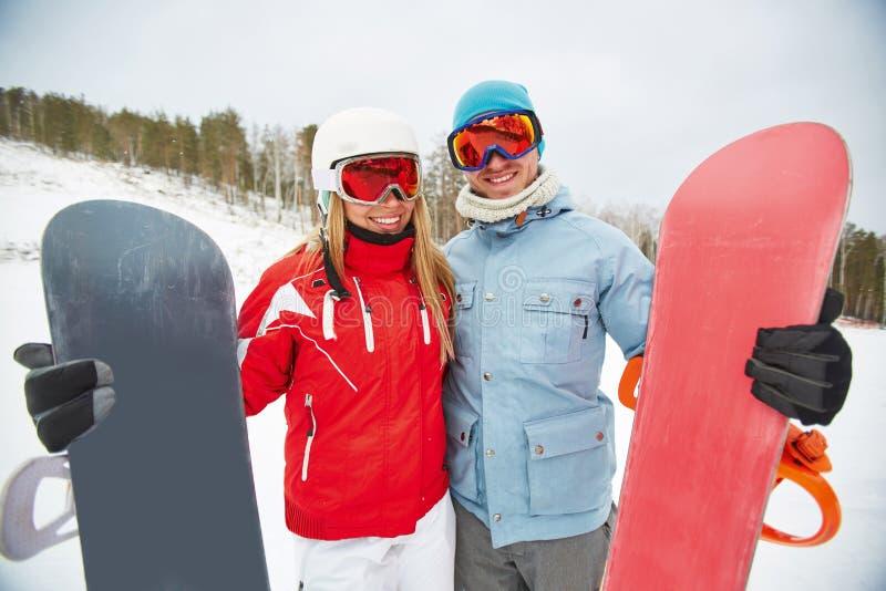 Pares felices con los snowboards fotos de archivo libres de regalías
