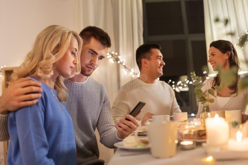 Pares felices con smartphone en la fiesta del t? de la familia imagen de archivo