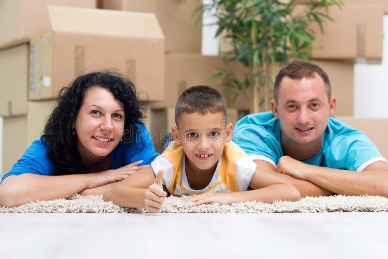 Pares felices con un niño en su nuevo hogar que pone en el piso w foto de archivo libre de regalías