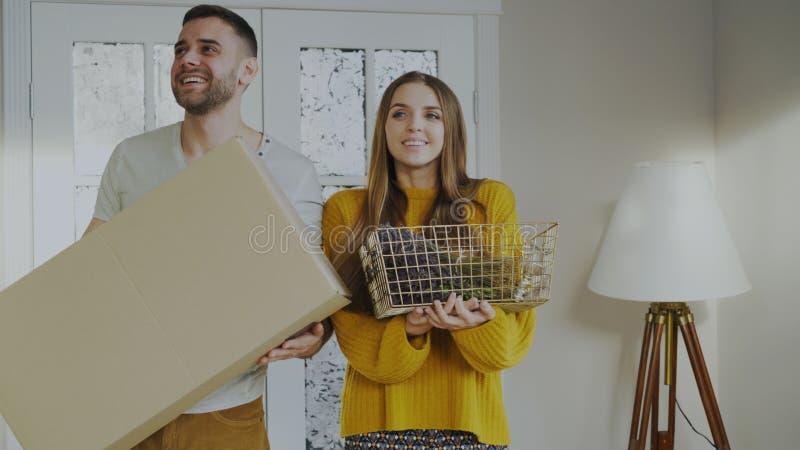 Pares felices felices de entrar en su nuevo hogar en la primera vez fotos de archivo
