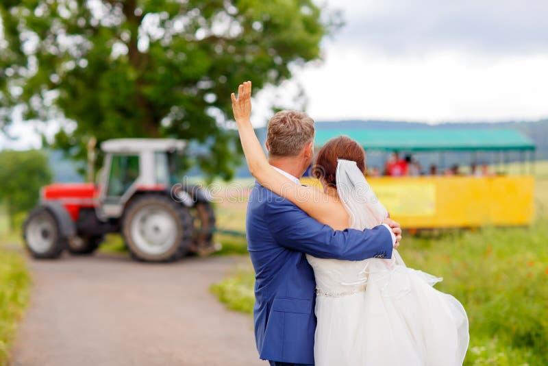 Pares felices de la boda con el tractor en fondo imágenes de archivo libres de regalías