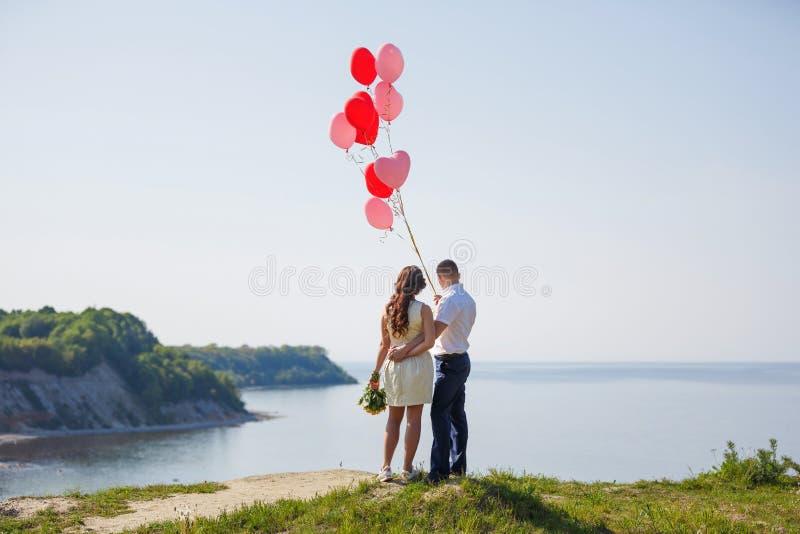 Pares felices de la boda con los globos rojos fotografía de archivo libre de regalías