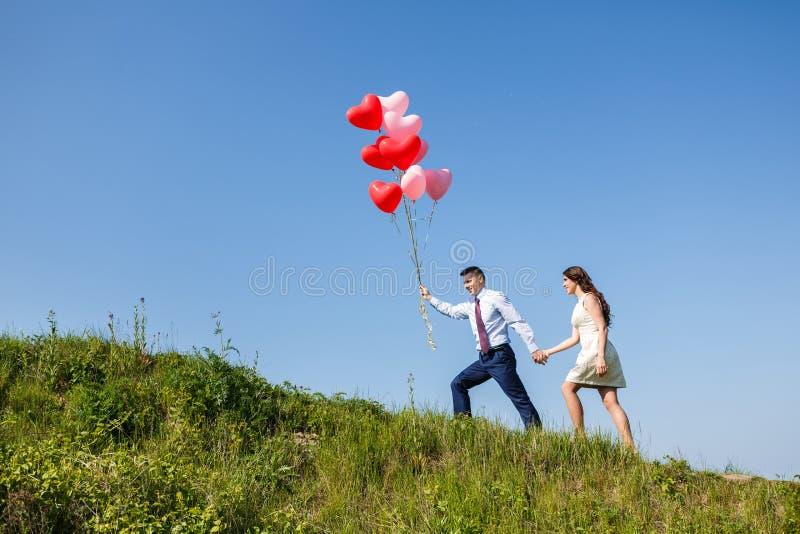Pares felices de la boda con los globos rojos imagen de archivo libre de regalías