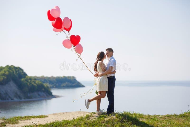 Pares felices de la boda con los globos rojos imágenes de archivo libres de regalías