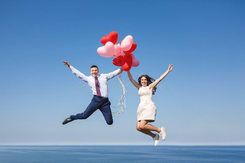 Pares felices de la boda con los globos rojos fotos de archivo libres de regalías