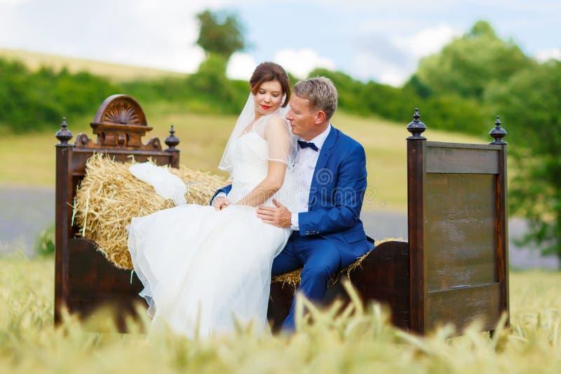 Pares felices de la boda en campo de trigo imagenes de archivo