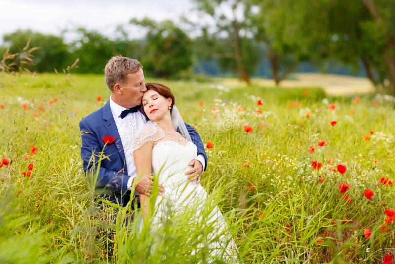 Pares felices de la boda en campo rosado de la amapola foto de archivo
