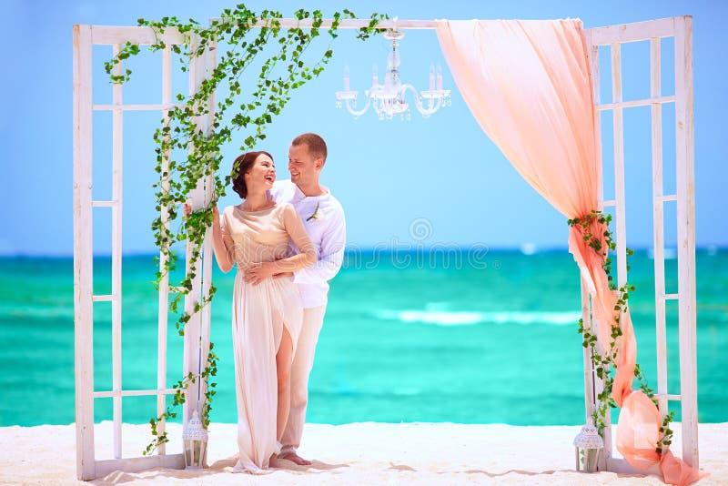 Pares felices de la boda en la playa tropical adornada fotos de archivo libres de regalías