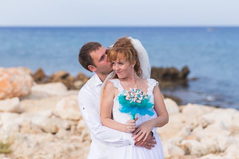 Pares felices de la boda en la playa del mar foto de archivo