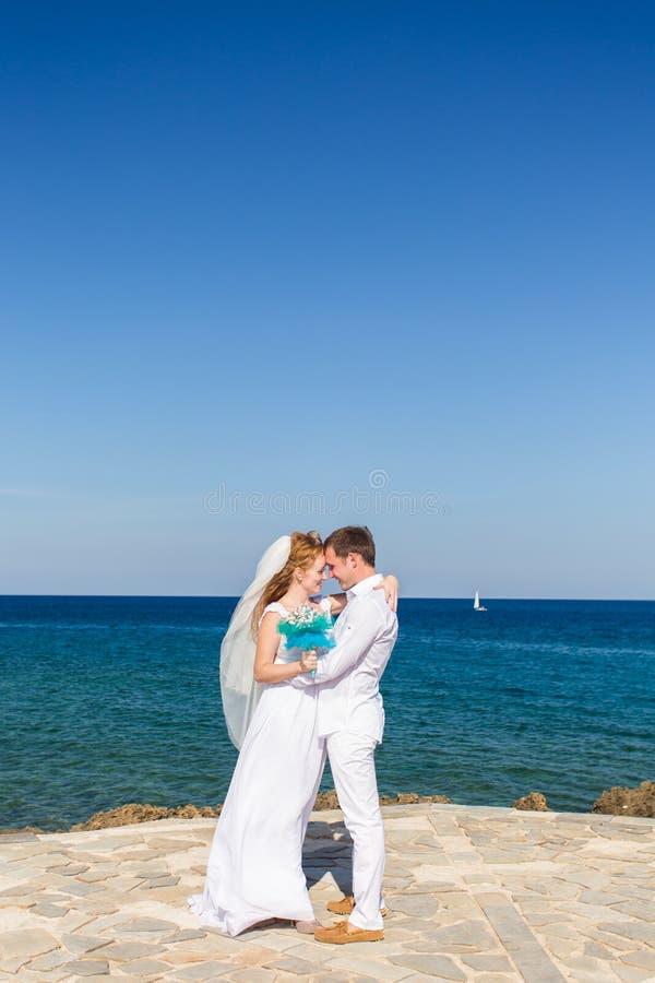 Pares felices de la boda en la playa del mar imagen de archivo libre de regalías