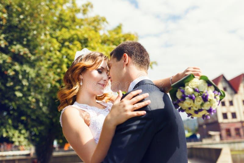 Pares felices de la boda en un parque fotos de archivo