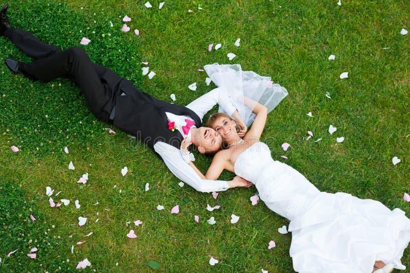 Pares felices de la boda que mienten en hierba verde fotografía de archivo libre de regalías
