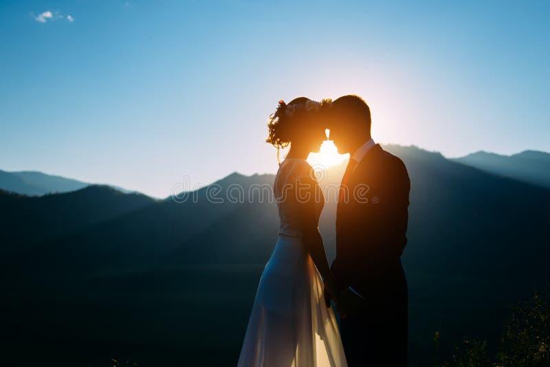 Pares felices de la boda que permanecen sobre el paisaje hermoso con las montañas durante puesta del sol foto de archivo