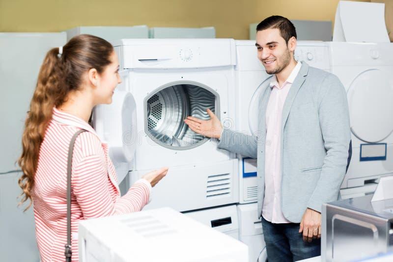 Pares felices de la familia que compran la nueva lavadora de ropa imagen de archivo libre de regalías