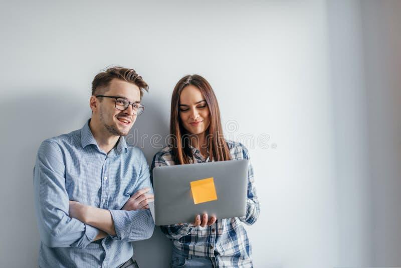 Pares felices de la mezcla-raza que sostienen el ordenador portátil mientras que se coloca y celebra aislado sobre fondo gris de  fotos de archivo libres de regalías