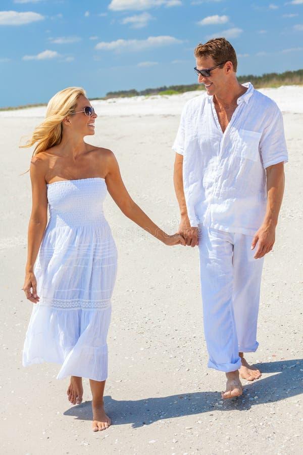 Pares felices de la mujer del hombre que llevan a cabo las manos que caminan en una playa imagen de archivo libre de regalías