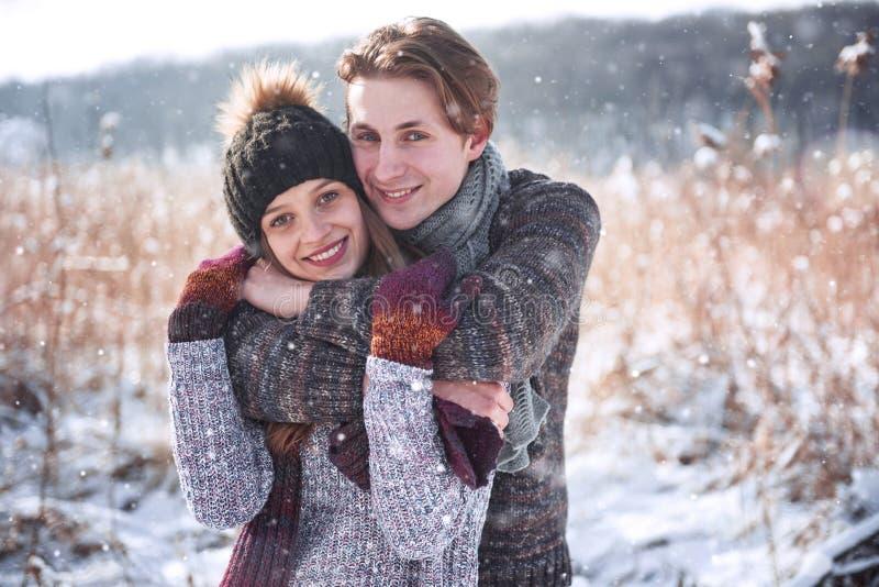 Pares felices de la Navidad en abrazo del amor en el bosque frío del invierno nevoso, espacio de la copia, celebración del partid fotografía de archivo libre de regalías