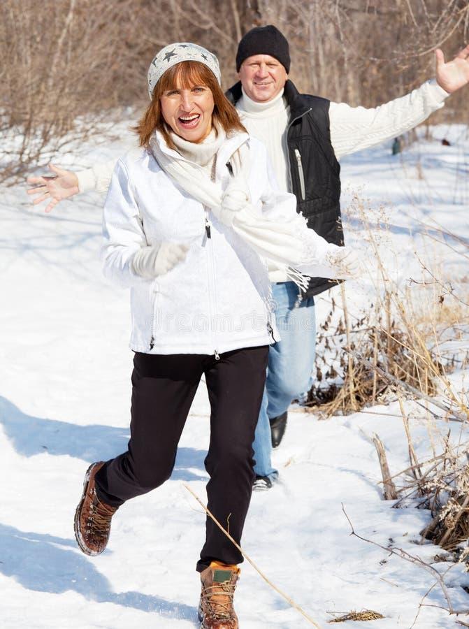 Pares felices de los mayores en parque del invierno imagenes de archivo