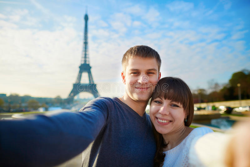 Pares felices de los turistas que toman el selfie en París fotos de archivo