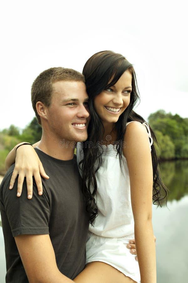 Pares felices del adolescente por el río imagenes de archivo