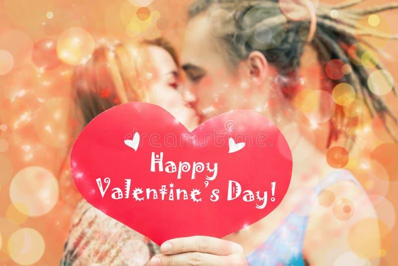 Pares felices del día de tarjetas del día de San Valentín que llevan a cabo símbolo rojo del corazón imagen de archivo libre de regalías