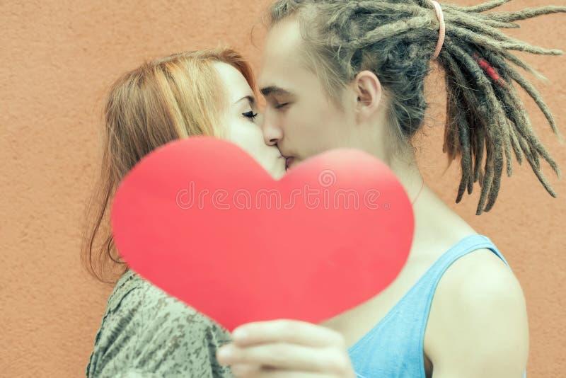 Pares felices del día de tarjetas del día de San Valentín que llevan a cabo símbolo rojo del corazón foto de archivo libre de regalías